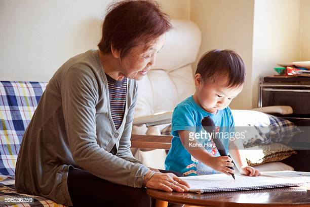 senior woman and baby boy drawing