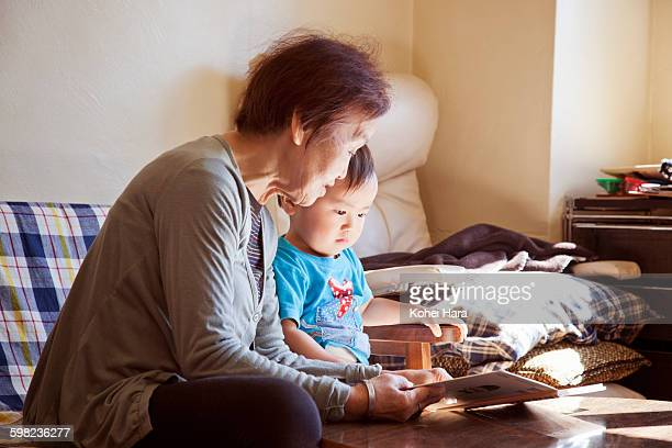 senior woman and baby boy reading a picture book