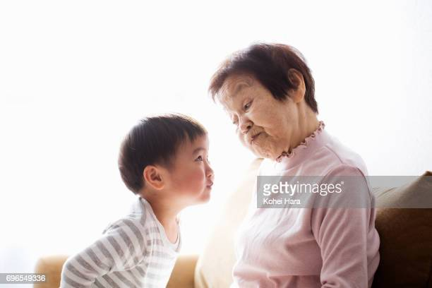 Senior woman and boy playing at home together