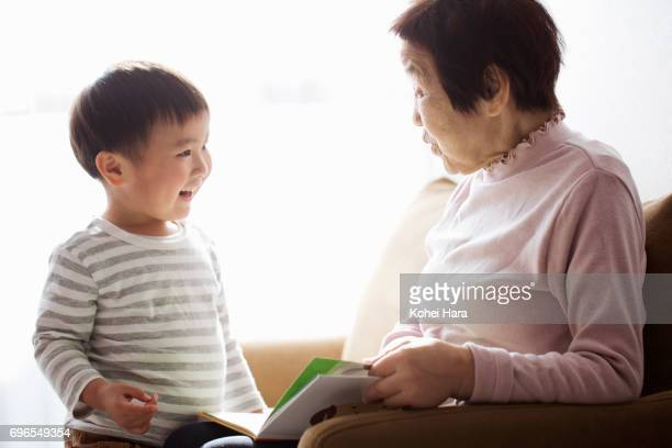 Senior woman and boy reading a book together