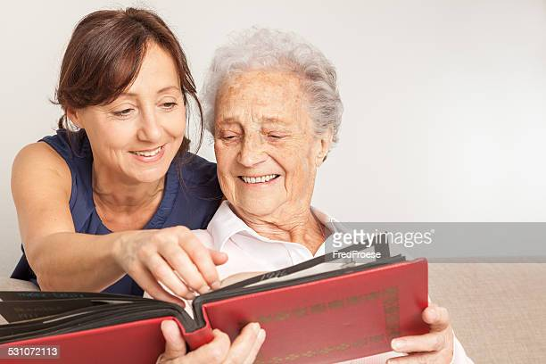 Senior woman and caregiver looking into photo album