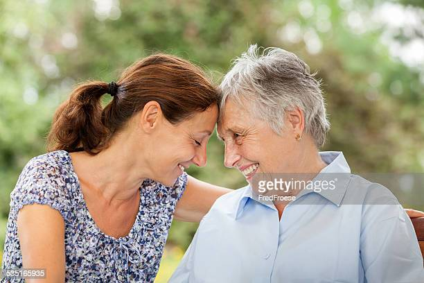 Senior woman and caregiver outdoors in a garden