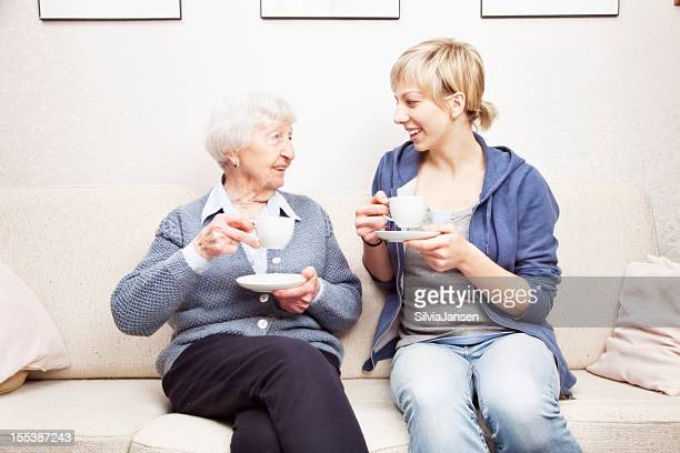 senior mujer hablando y bebiendo café cuidador