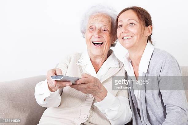 Mujer mayor y cuidadores viendo televisión