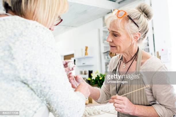 Senior woman and colleagues working with porcelain clay