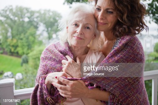 Senior woman and daughter embracing on porch, portrait : Stock Photo