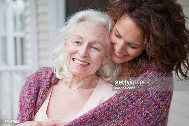 Senior woman and daughter embracing on porch, portrait