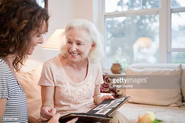 Senior woman and daughter looking through photo album