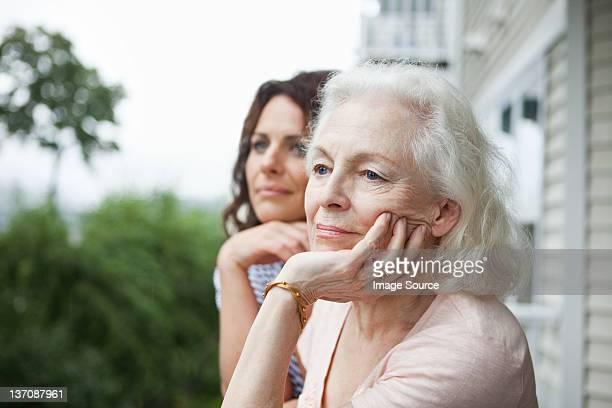Mulher idosa e filha relaxante no porch