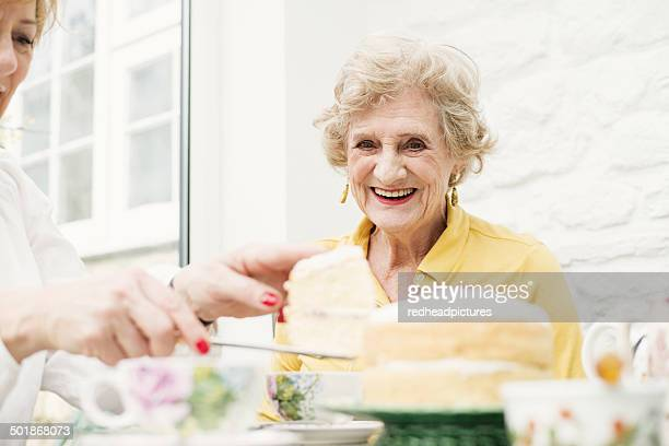 Senior woman and daughter, slicing cake