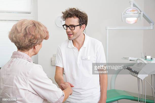 Senior woman and dentist shaking hands in surgery