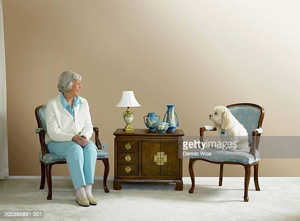 Senior woman and dog sitting on armchairs in living room