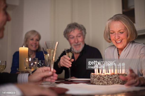Senior woman and friends with birthday cake