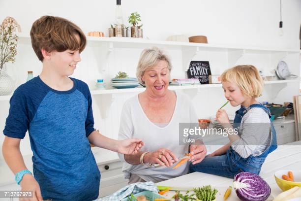 Senior woman and grandchildren preparing vegetables at kitchen table