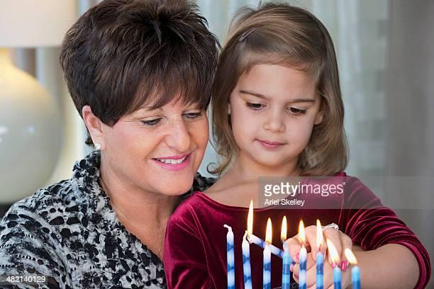 Senior woman and granddaughter lighting Hanukah menorah