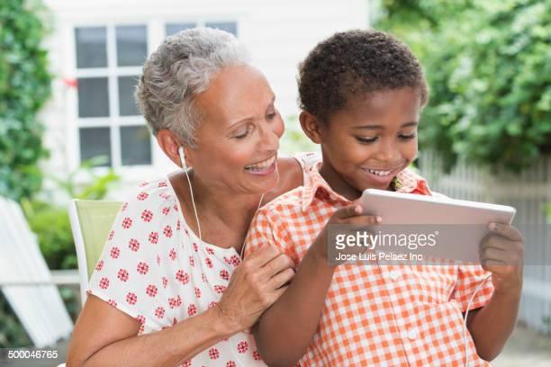 Senior woman and grandson using digital tablet