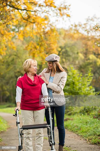 Senior woman and her adult granddaughter walking together in autumnal park