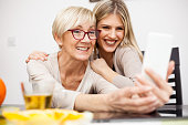 Senior mother and her daughter smiling and posing for a selfie while sitting by dinner table in bright room. Mother holding phone. Happy family moments at home.