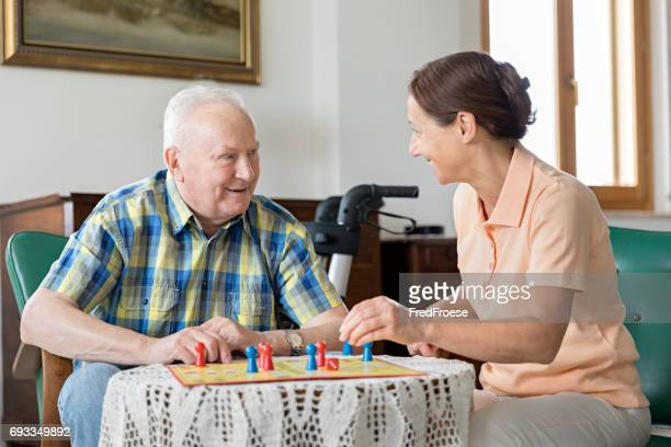 Senior woman and home caregiver playing board game