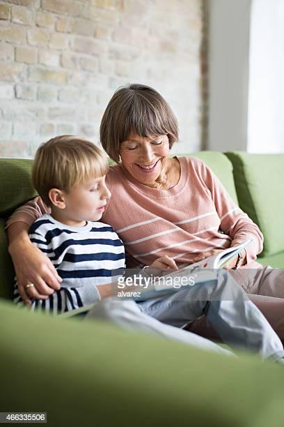 Senior Frau und kleine Junge sitzt auf sofa lesen Buch