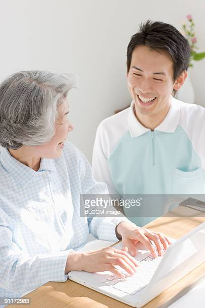 Senior woman and male care worker smiling at each other