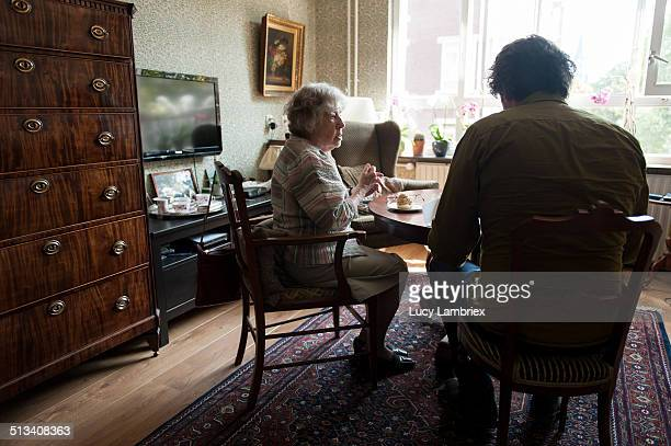 Senior woman and man having coffee in livingroom