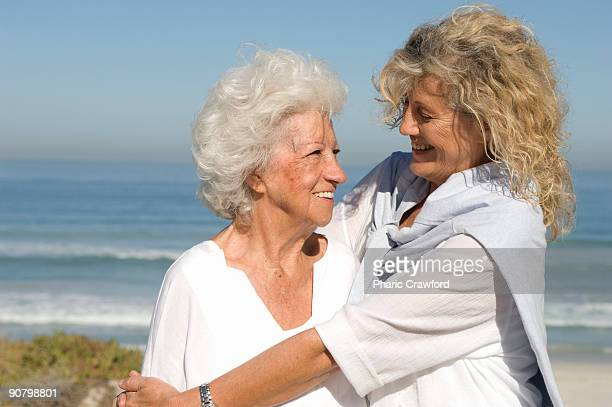 Senior woman and mature woman hugging and looking at each other on beach, Table View, Cape Town, Wes