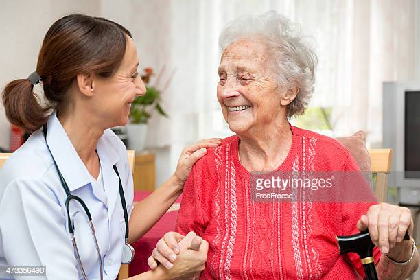 Senior woman and nurse holding hands