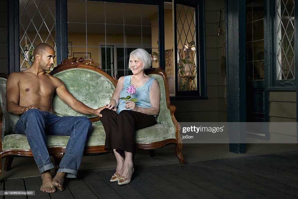 Senior woman and young man sitting on porch holding hands : Stock Photo