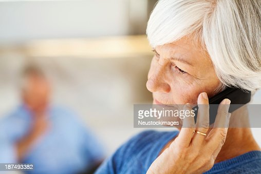 Senior Woman Answering Smart Phone With Man In Background