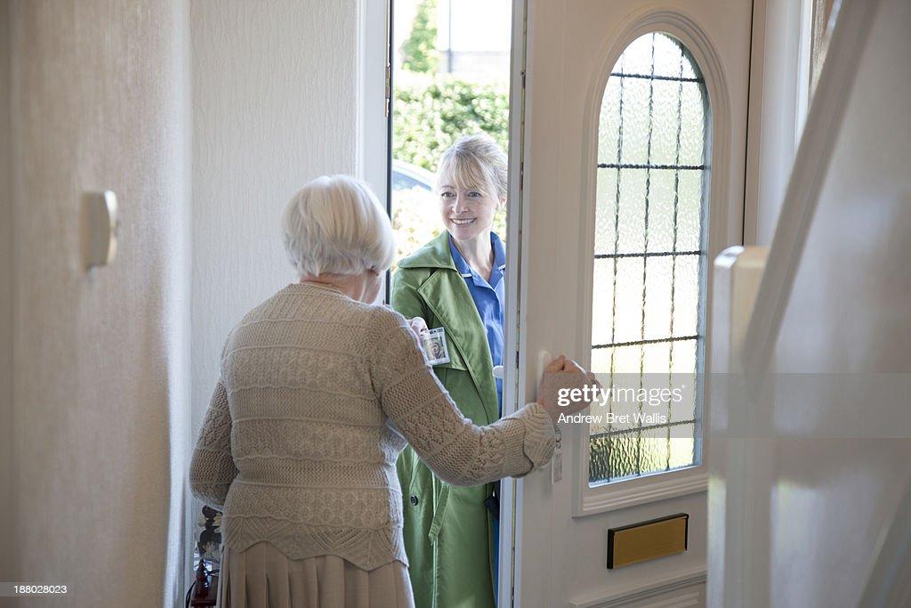 Senior woman answers door to community careworker : Stock Photo