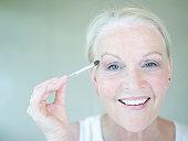 Senior woman applying eye make up, close up