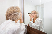 Senior woman applying eyeliner while looking at mirror in bathroom