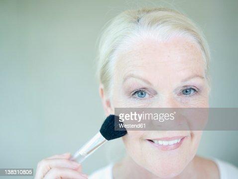 Senior woman applying make up, close up