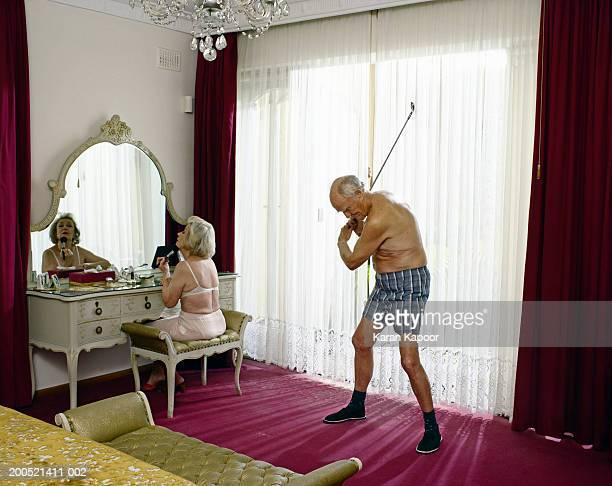 Senior woman applying makeup and senior man swinging golf club