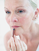 Senior woman appyling lipstick, close up