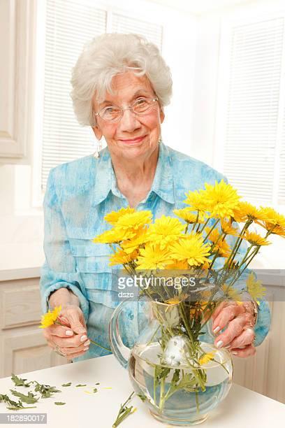 senior woman arranging cut yellow flowers in vase