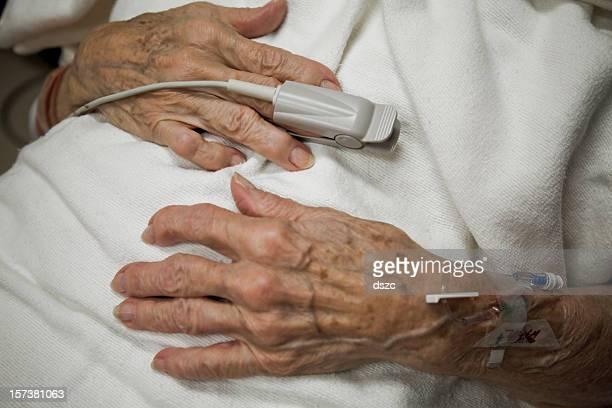 Mujer senior artritis manos, oxígeno sensor, gota a gota, ER hospital