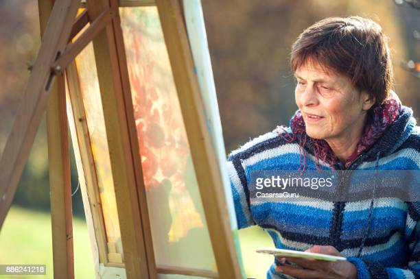 Senior Woman Artist Painting Artwork on Canvas