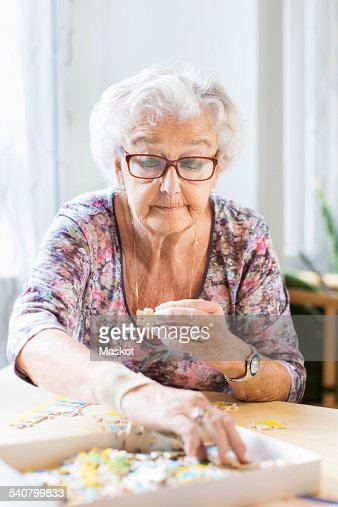 senior woman assembling jigsaw pieces at table in nursing home photo getty images. Black Bedroom Furniture Sets. Home Design Ideas