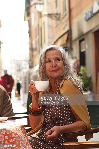 Senior woman at a sidewalk cafe, Italy