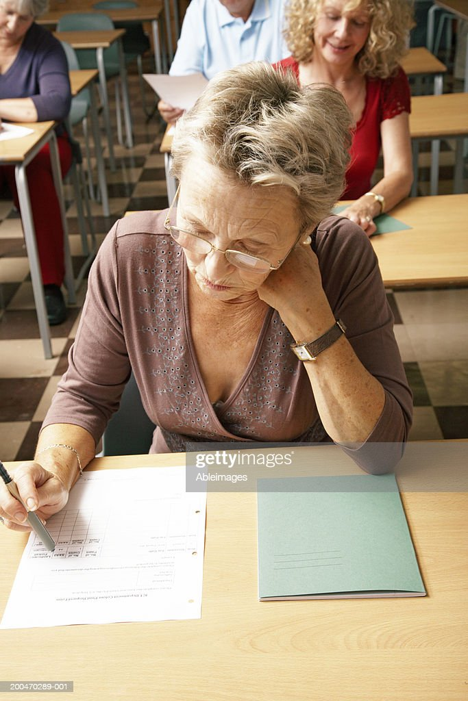 Senior woman at desk in examination hall : Stock Photo