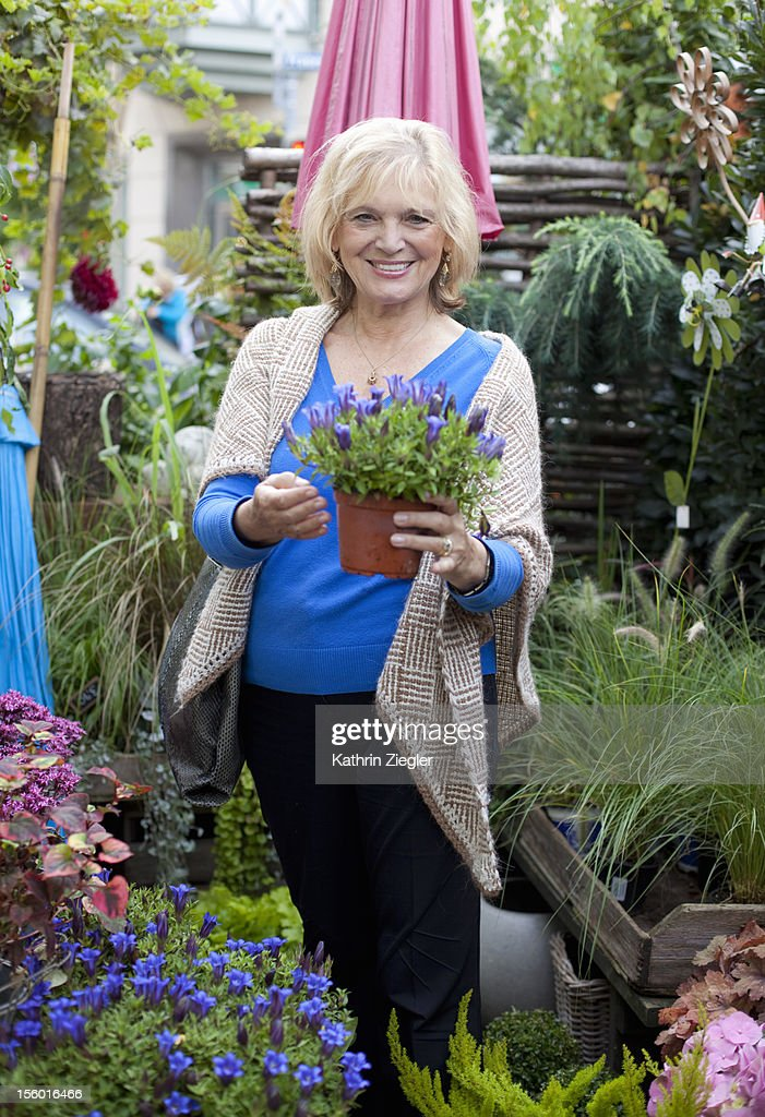 senior woman at garden shop, holding flower pot : Stock Photo