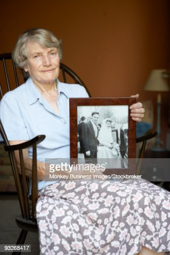 Senior Woman At Home Looking At Old Wedding Photo : Stock Photo