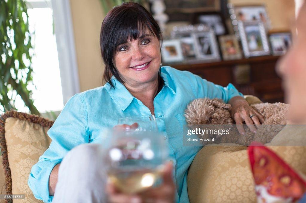 Senior woman at home, sitting on sofa, talking to friend