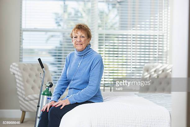Senior woman at home with portable oxygen tank