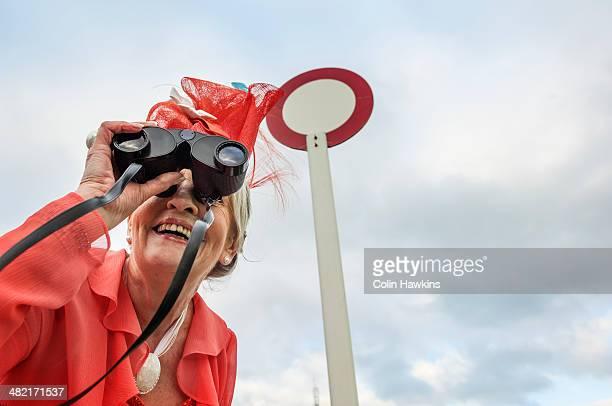 Senior woman at races leaning forward and looking through binoculars