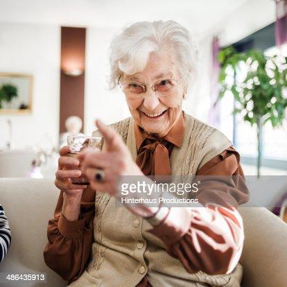 senior woman at sofa having fun stock photo getty images. Black Bedroom Furniture Sets. Home Design Ideas