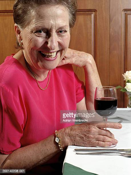 Senior woman at table in restaurant, holding glass, smiling, portrait
