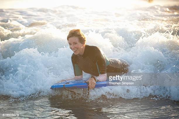 senior woman at the beach with her body board